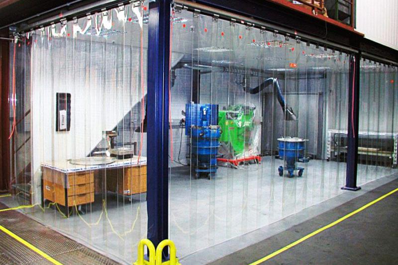 Kurtyny przemysłowe wygradzające stanowiska pracy na hali produkcyjnej