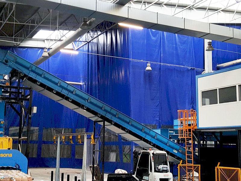 Kurtyny plandekowe osłaniające maszyny na hali produkcyjnej - funkcja przeciwpyłowa